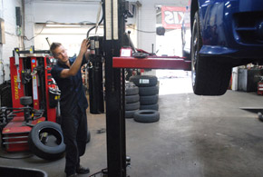 car in service bay with technician
